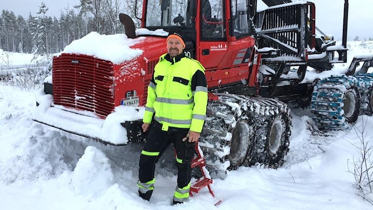 Lars Magnusson ute i skogen vid sitt arbetsfordon.