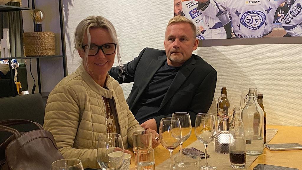 En kvinna och men sitter vid ett bord uppdukat med tomma glas. I bakgrunden skymtar man ishockeyspelare från Leksands IF på en tavla.