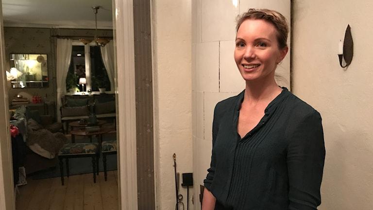Erika Ågren står framför sin kakelugn
