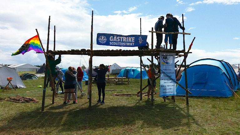 En grupp ungdomar hjälps åt att bygga en portal av trä. En prideflagga samt en vepa med texten Gästrike scoutdistrikt hänger från den. I bakgrunden står tält uppställda.