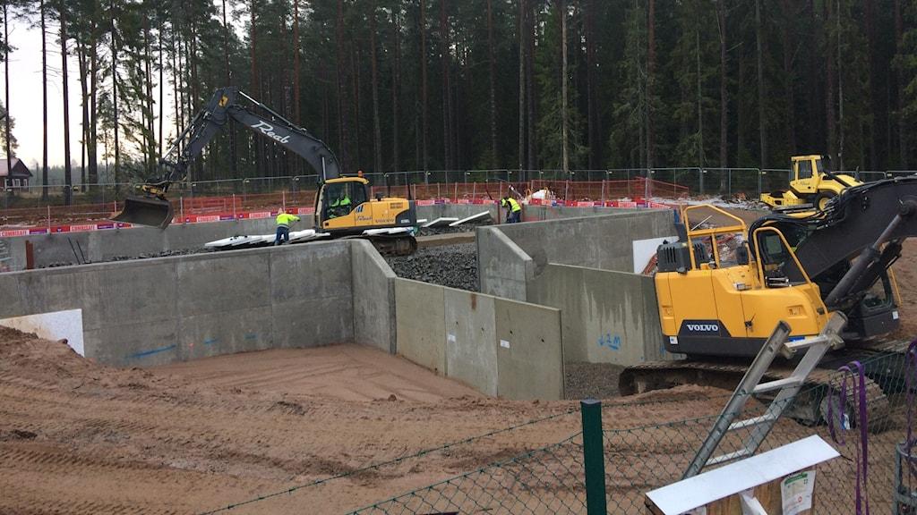 Grävmaskiner som håller på att bygga dammen.