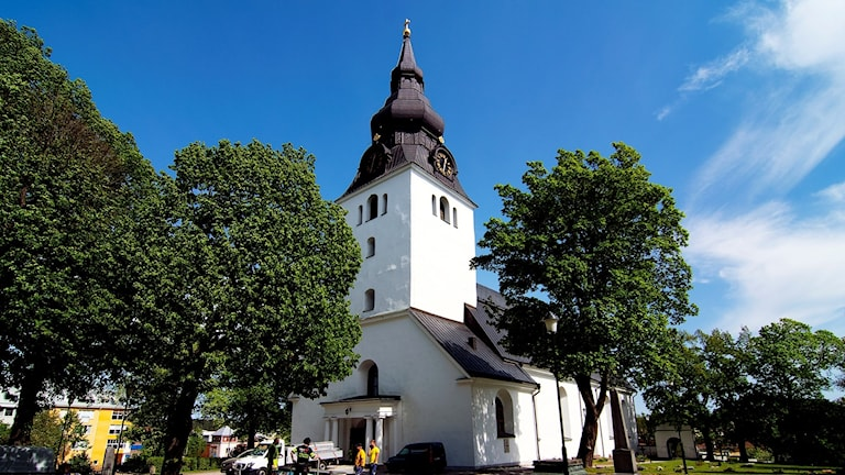 Vitkalakad kyrka med högt lökkupoltorn med tornur.