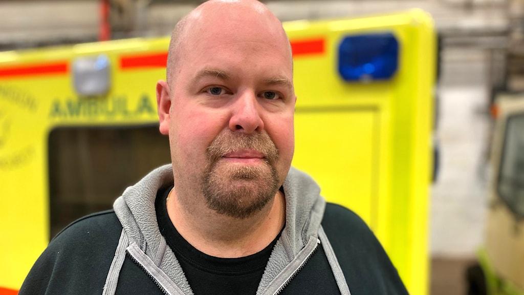 En man står framför en ambulans