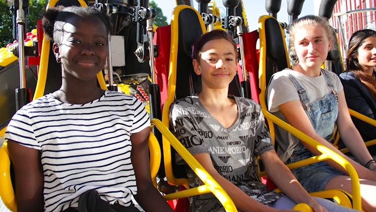 Sirra sawo och hennes kompisar sitte ri en karusell beredda att åka