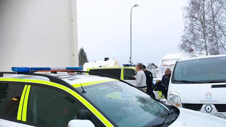 den misstänkte förs in i rättssalen i Hudiksvalls tingsrätt. Han är klädd i vit, långärmad t-shirt och beiga chinos. polisbilar står runt omkring samt en bil från kriminalvården.