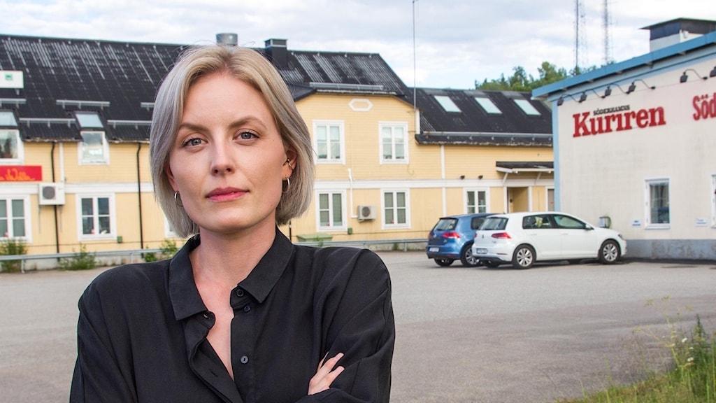 En kvinnlig chefredaktör står utanför en byggnad där de gör Söderhamns-kuriren.