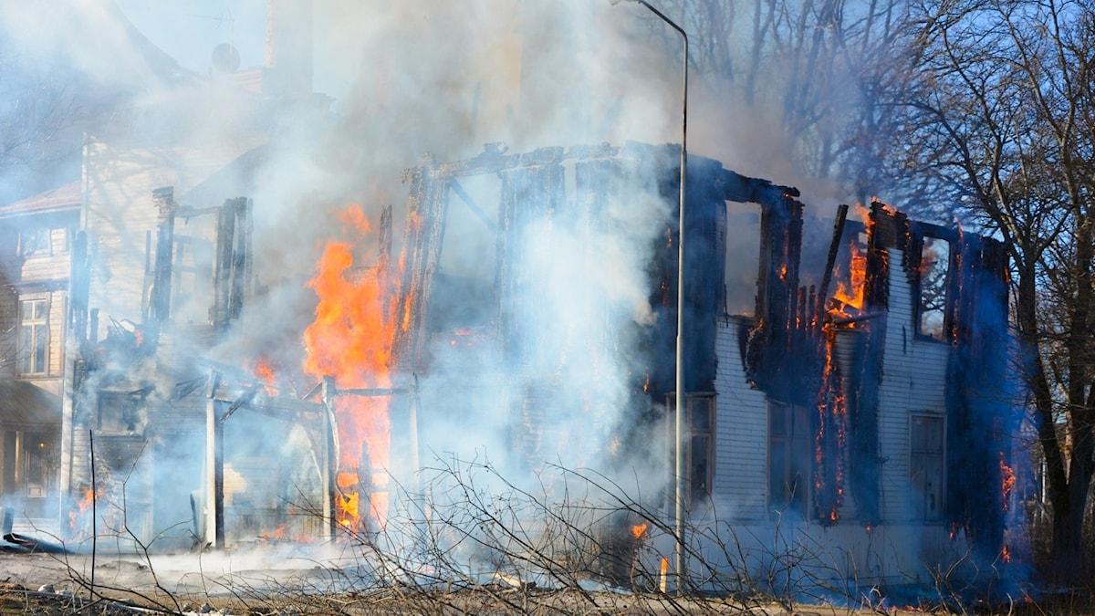 Ett flerfamiljshus i Ockelbo av trä som är täckt av rök. Det är nästan nedbrunnet och taket saknas. Det är stora gula eldslågor i byggnaden