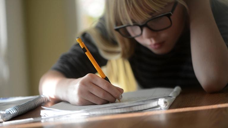 Flicka med glasögon som gör sina läxor vid ett skrivbord