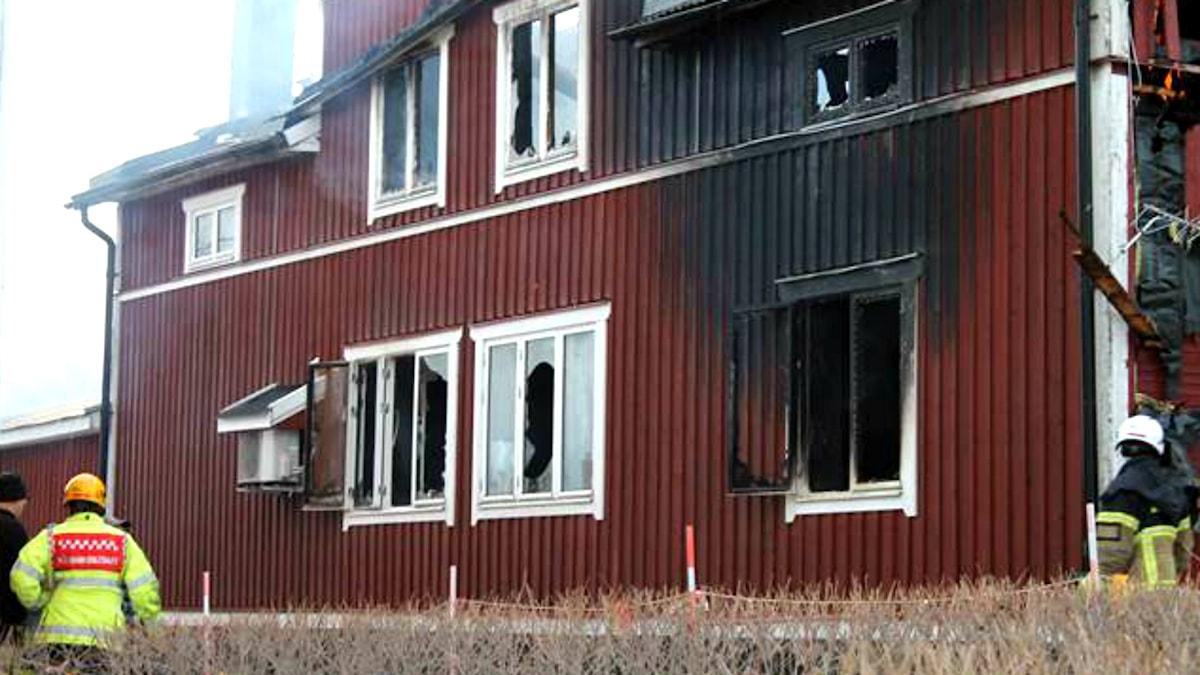 Ett stort rött hus som är brandskadat.